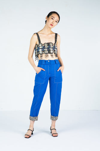 Model wears tailored blue pants with leopard print cuffs and an embellished bralette
