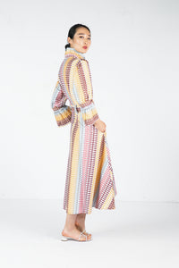 Side profile of model wearing midi length printed dress with matching belt, high frill collar and exaggerated flared cuffs