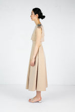 Load image into Gallery viewer, Side view of model wearing full length sleeveless tan dress with embroidered shoulder detail