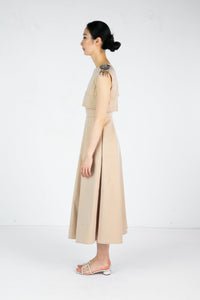 Side view of model wearing full length sleeveless tan dress with embroidered shoulder detail
