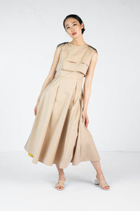 Model wears full length sleeveless tan dress with embroidered shoulder detail