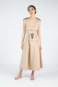 Model wears sleeveless tan dress with embroidered shoulder detail and embroidered belt
