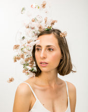 Load image into Gallery viewer, A woman wearing a fascinator with pastel silk petals hanging on silver wire to her shoulder off a metallic gold headband