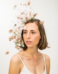 A woman wearing a fascinator with pastel silk petals hanging on silver wire to her shoulder off a metallic gold headband