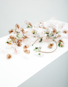 A fascinator lying down with pastel silk petals hanging on silver wire off a metallic gold headband