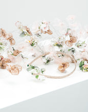 Load image into Gallery viewer, A close up of a fascinator with pastel silk petals hanging on silver wire off a metallic gold headband
