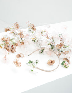 A fascinator with pastel silk petals hanging off a metallic gold headband