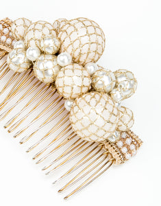 A close up of gold metal hair comb with a cluster of hand wrapped pearls