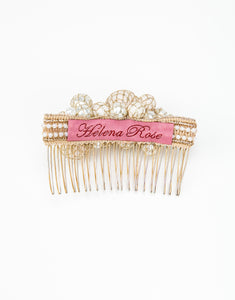 The back of a gold metal hair comb with a cluster of hand wrapped pearls and a pink Helena Rose label