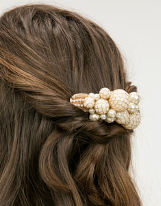 A close up of a hair comb with a cluster of hand wrapped pearls in a woman's hair