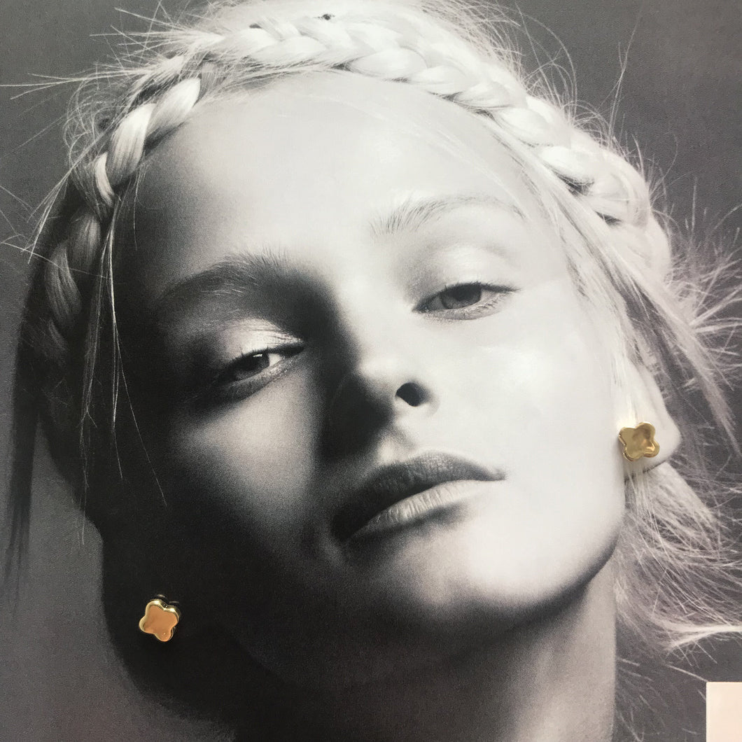 Gold stud earrings on black and white photograph of model