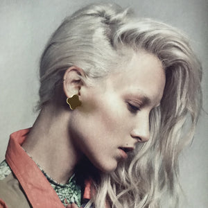 Gold stud earring on photograph of model