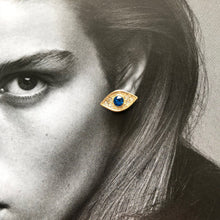 Load image into Gallery viewer, Close up of gold evil eye stud with blue crystal laid on black and white photo of model