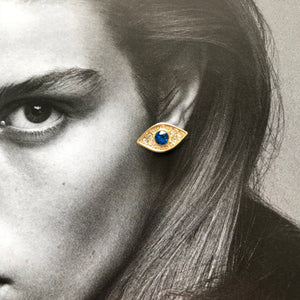 Close up of gold evil eye stud with blue crystal laid on black and white photo of model