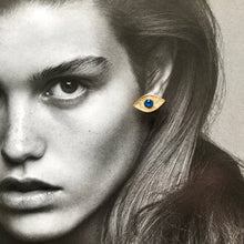 Load image into Gallery viewer, Gold evil eye studs with blue crystal laid on black and white photo of model