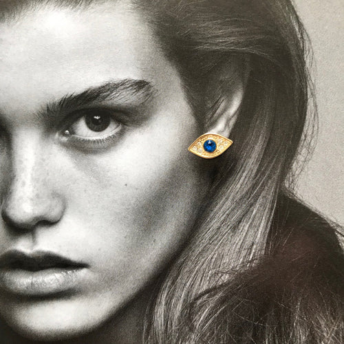 Gold evil eye studs with blue crystal laid on black and white photo of model