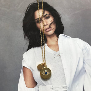 Gold necklace with evil eye charm laid on photograph of Kim Kardashian