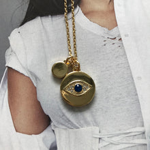 Load image into Gallery viewer, Close up of gold necklace with evil eye charm on photograph of model