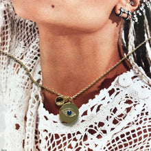 Load image into Gallery viewer, Gold necklace with evil eye charm laid on photograph of models neck