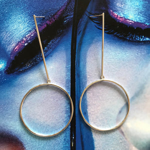 Silver drop earrings with circle detail laid on blue photo of model