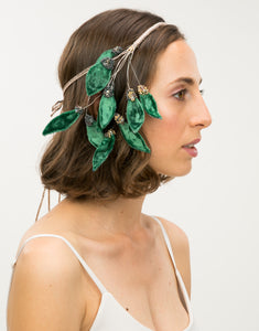 Side profile of model wearing beaded headband with velvet green leaves