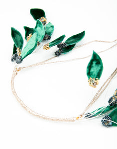 Close up flat lay of beaded headband with green velvet leaf details