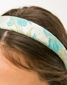 Close up of a model wearing a blue and gold floral brocade headband