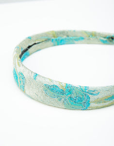 Close up of a floral blue and gold brocade headband