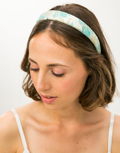 Top view of model wearing a blue and gold brocade headband