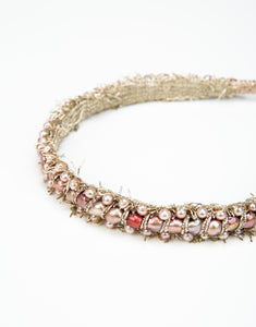Close up of pink pearl embellishments on a gold headband