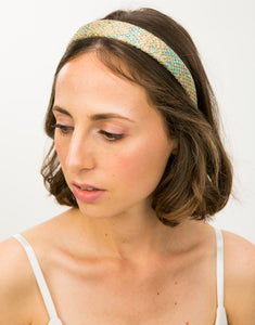 Close up of model wearing gold and blue brocade headband with gold netting overlay