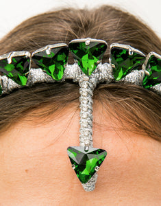 Close up of silver headband embellished with green triangle crystals and forehead detail