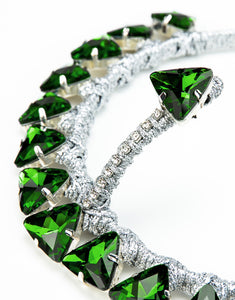 Close up of silver headband embellished with green triangle crystals
