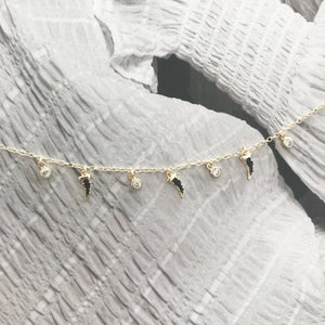 Gold choker with white sapphire and black spinel charms on old photograph
