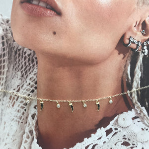 Gold choker with white sapphire and black spinel charms on photograph of womans neck
