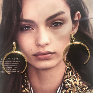 Gold C shape drop earrings laid on photo of model