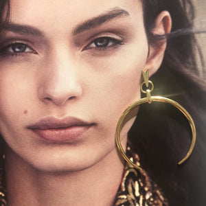 Gold C shape drop earring laid on photo of model