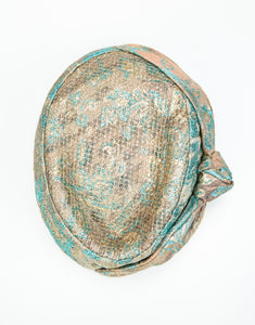 top view of jacquard pillbox hat with knot detail and gold netting