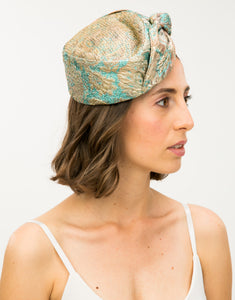 Side view of a model wearing a jacquard pillbox hat with knot detail