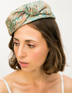 Model wearing a Jacquard pillbox hat with knot detail