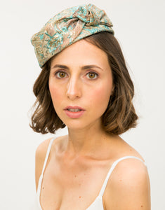 Front view of model wearing a jacquard pillbox hat with knot detail
