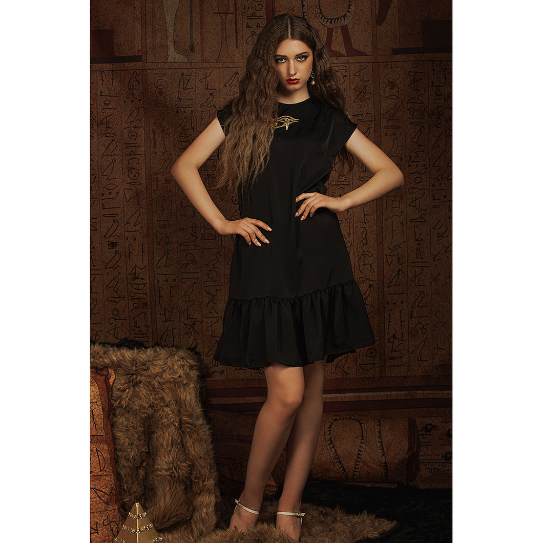 Model wears black babydoll dress with gold Eye of Ra embroidery