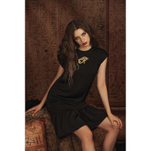 Load image into Gallery viewer, Model sits in black babydoll dress with gold Eye of Ra embroidery