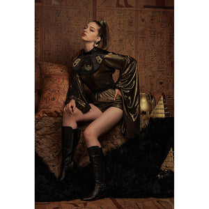 Sitting model wears metallic gold dress with oversized sleeves in front of Egyptian hieroglyphs