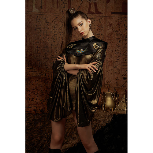 Model wears metallic gold dress with oversized sleeves in front of Egyptian hieroglyphs