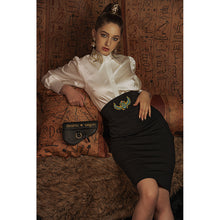 Load image into Gallery viewer, Model reclines in white blouse with Eye of Ra embroidery on the collar with a black skirt