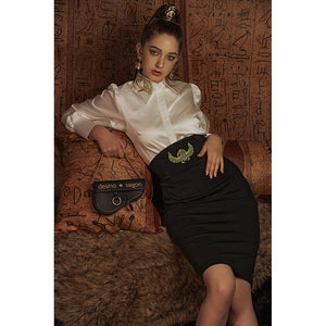 Model reclines in white blouse with Eye of Ra embroidery on the collar with a black skirt