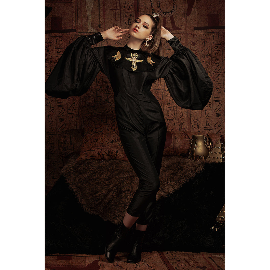 Woman wears a black jumpsuit with Egyptian-style embroideries on the collar and oversized sleeves