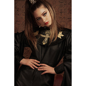 Close up of woman in a black jumpsuit with Egyptian-style embroideries on the collar