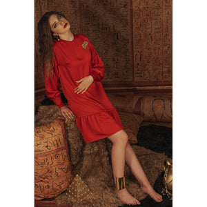 Model reclines in red baby doll dress with Eye of Ra embroidery detail